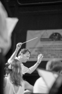 picture of Glenn Quader, second music director of PSO, directing a performance